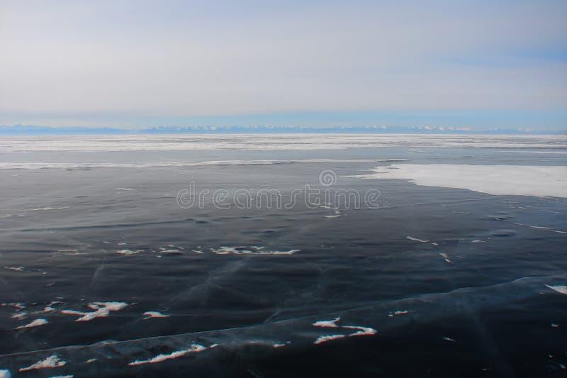 Escuro grosso - gelo azul do lago da montanha no inverno fotografia de stock royalty free