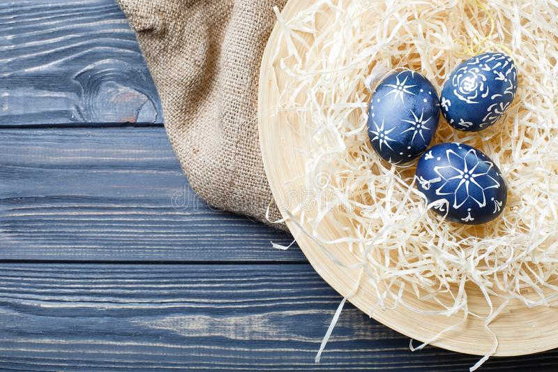 Escuro pintado à mão - ovos da páscoa azuis no ninho e nas flores fotos de stock royalty free