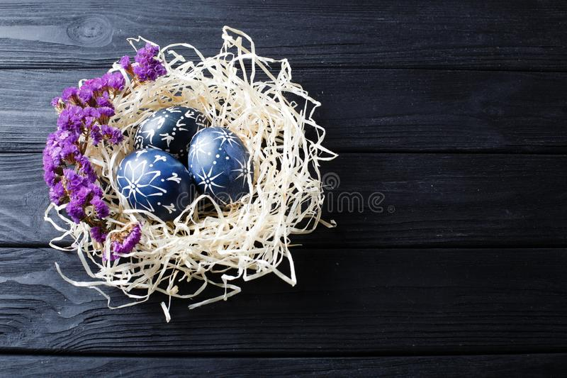 Escuro pintado ? m?o - ovos da p?scoa azuis no ninho e nas flores imagem de stock
