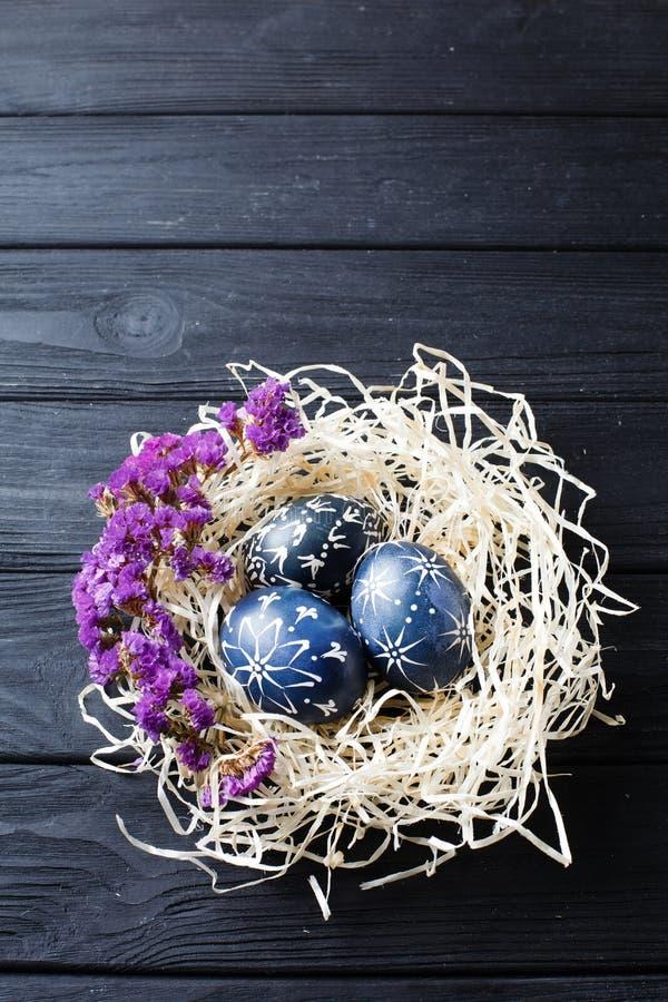 Escuro pintado ? m?o - ovos da p?scoa azuis no ninho e nas flores foto de stock