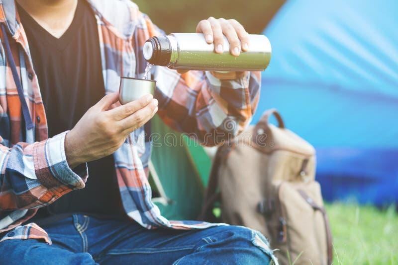 Escursione del viaggiatore con zaino e sacco a pelo dell'uomo che si siede campeggio anteriore della tenda immagine stock