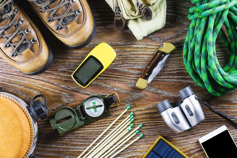 Escursione dell'attrezzatura con gli stivali, bussola, binocolo, partite, borsa di viaggio su fondo di legno Concetto attivo di s fotografie stock libere da diritti