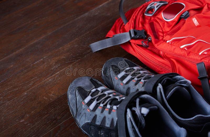 Escursione dell'attrezzatura: stivali di trekking e dello zaino sui bordi di legno immagini stock
