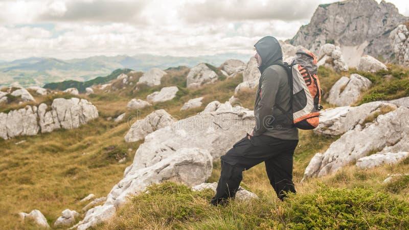Escursione dell'uomo con lo zaino sulla cresta della montagna che guarda il picco di montagna fotografia stock libera da diritti