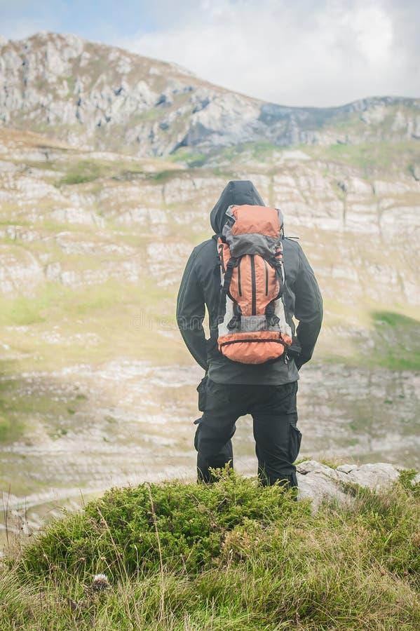 Escursione dell'uomo con lo zaino sulla cresta della montagna che guarda il picco di montagna immagini stock