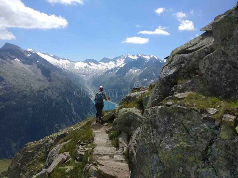 Escursione della ragazza con lo zaino che gode della vista dalle montagne e dal lago immagini stock