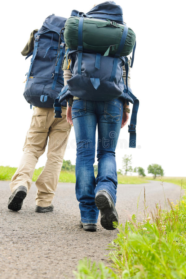 Escursione dello zaino dei piedini delle coppie sulla strada asfaltata immagine stock libera da diritti