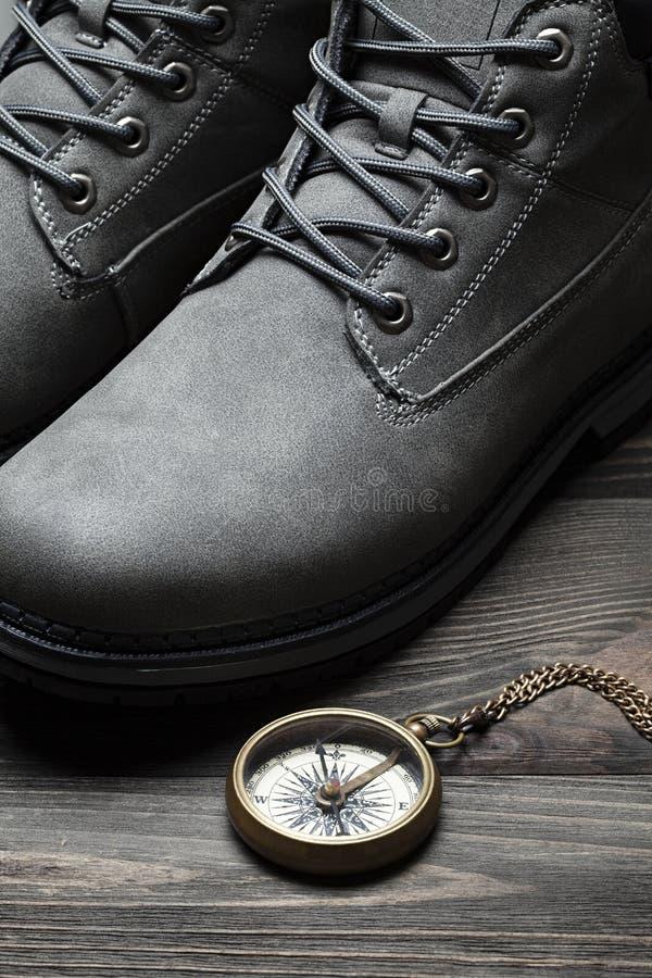 Escursione gli stivali e della bussola d'annata su fondo di legno immagine stock libera da diritti