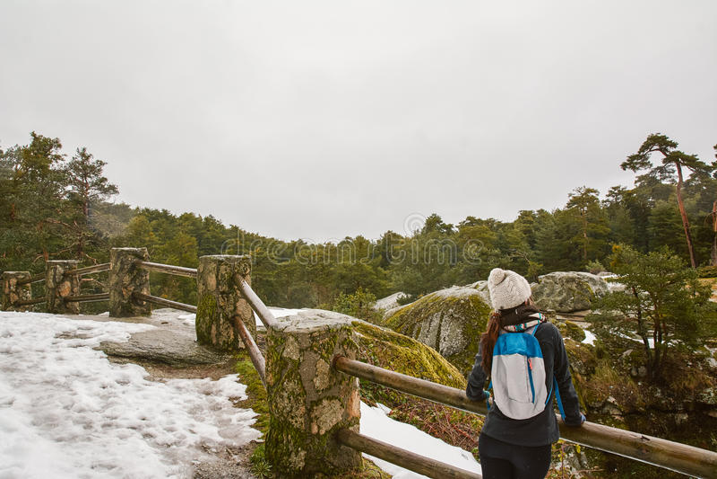 Escursione - viandante della donna che gode del paesaggio nella foresta nevosa L fotografia stock libera da diritti