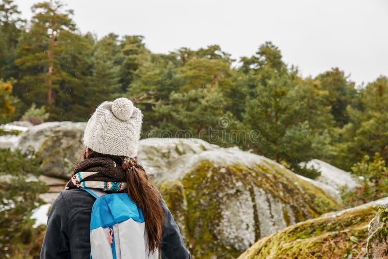 Escursione - viandante della donna che gode del paesaggio nella foresta nevosa L fotografie stock libere da diritti
