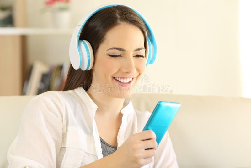 Escuta adolescente feliz a música usando um smartphone azul foto de stock royalty free