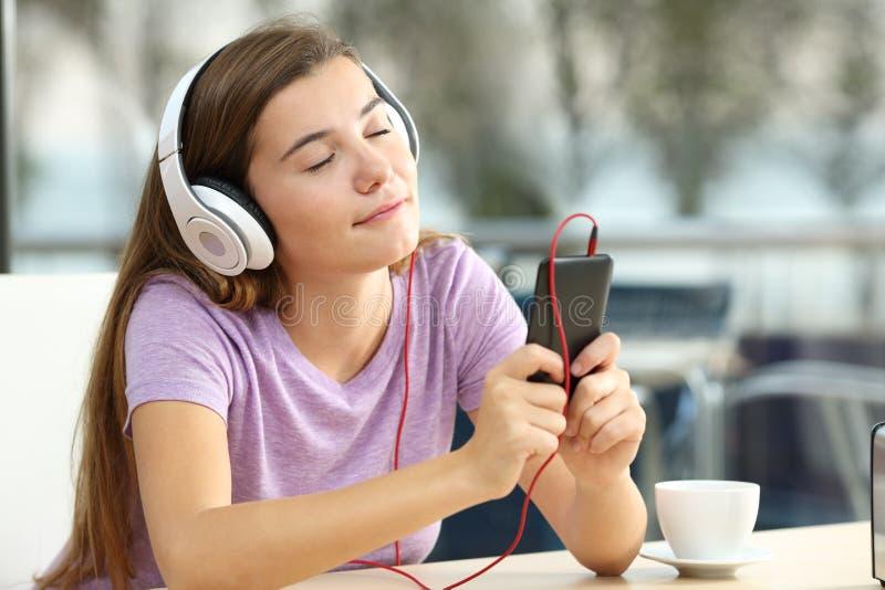 Escuta adolescente relaxado a música em uma barra fotografia de stock