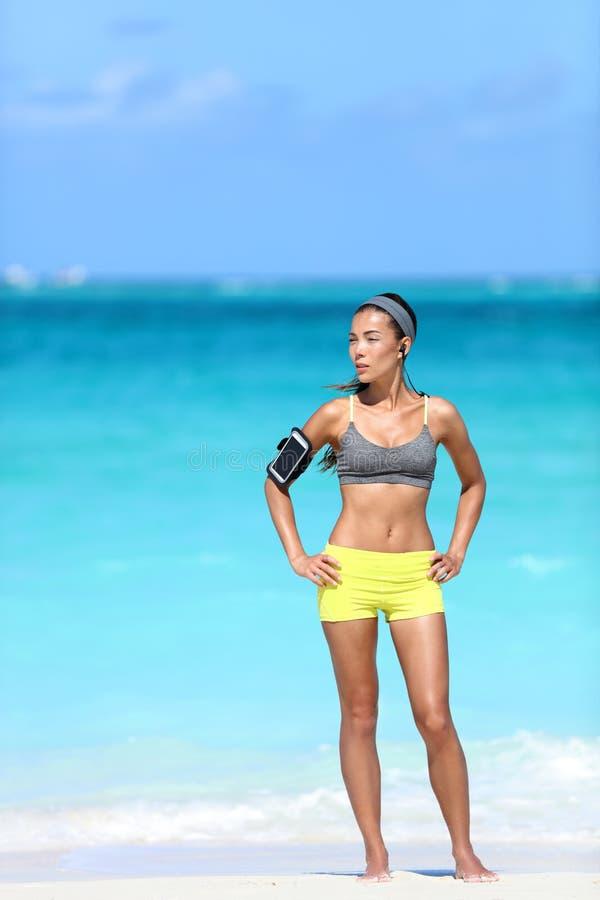 Escuta de corrida da mulher apta do corpo a música da motivação com fita do telefone foto de stock