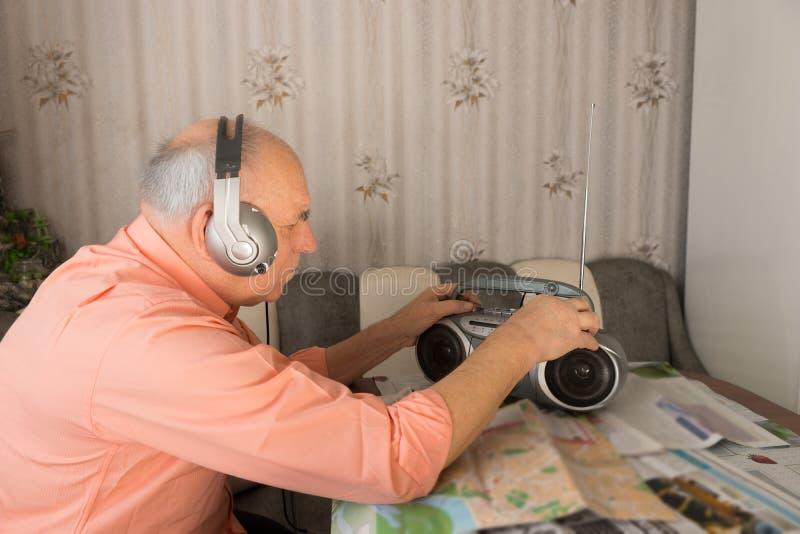 Escuta idosa no rádio com auriculares fotografia de stock royalty free