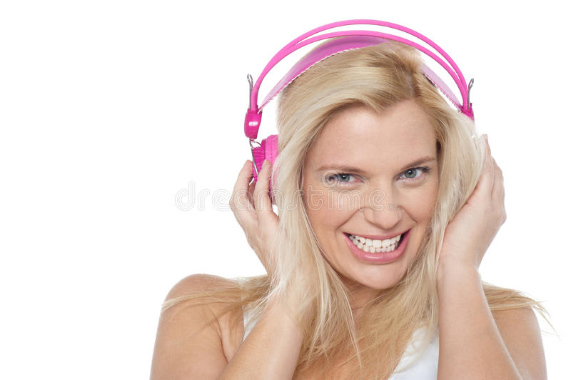 Escuta loura quente a música através dos auscultadores imagens de stock