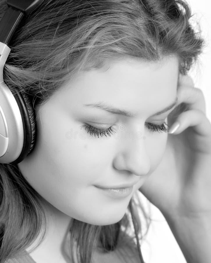 Escuta a música com auscultadores foto de stock