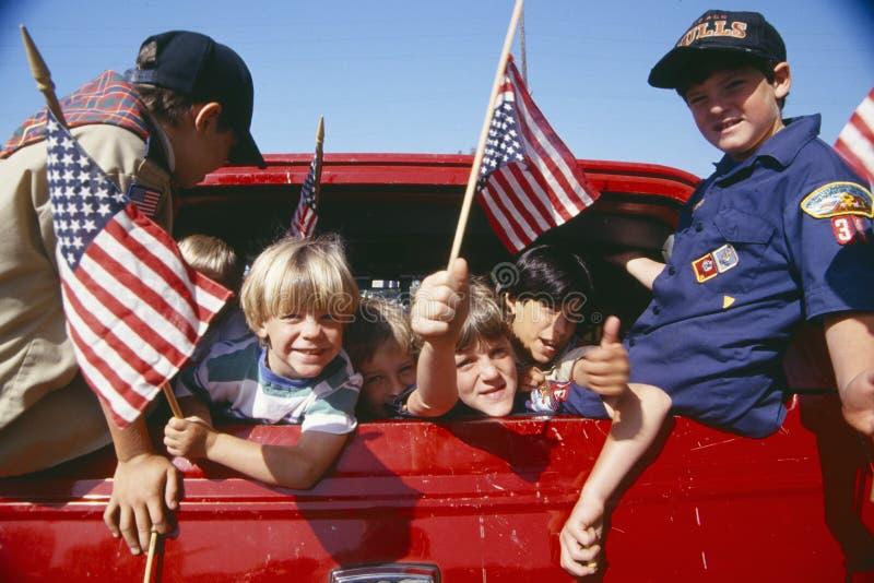 Escuteiros de Cub que acenam bandeiras americanas imagens de stock