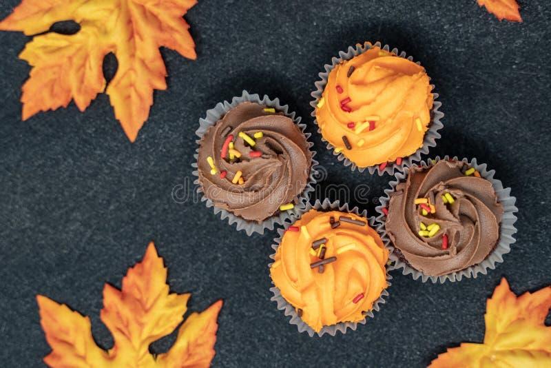 Esdoornbladeren en Halloween Cupcakes op zwarte achtergrond stock foto's