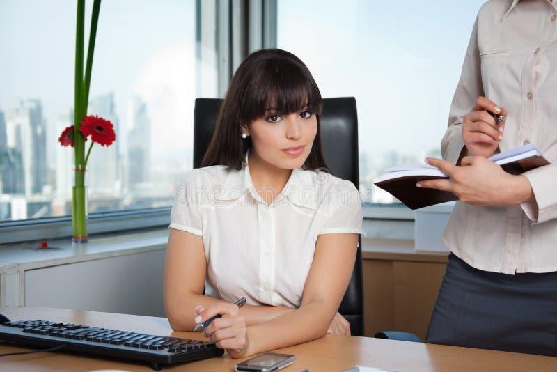 Esecutivo femminile con l'assistente sul lato immagini stock libere da diritti