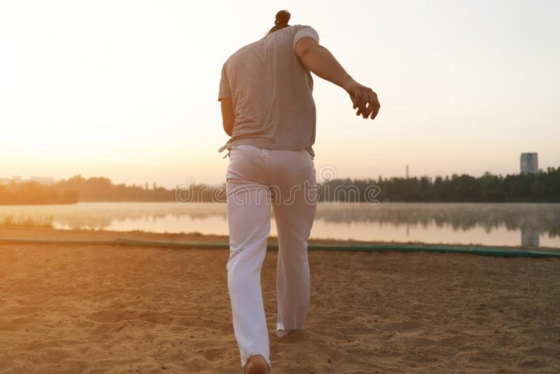 Esecutore atletico di capoeira che fa i movimenti sulla spiaggia fotografie stock