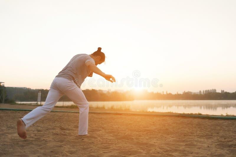 Esecutore atletico di capoeira che fa i movimenti sulla spiaggia immagine stock