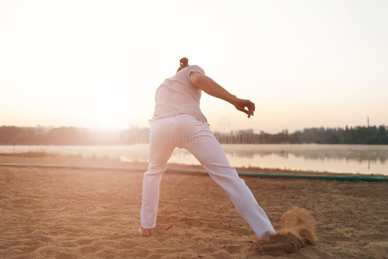Esecutore atletico di capoeira che fa i movimenti sulla spiaggia fotografie stock libere da diritti