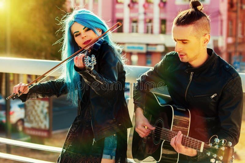 Esecutori della via di musica con paesaggio urbano di tramonto del violinista della ragazza fotografie stock libere da diritti
