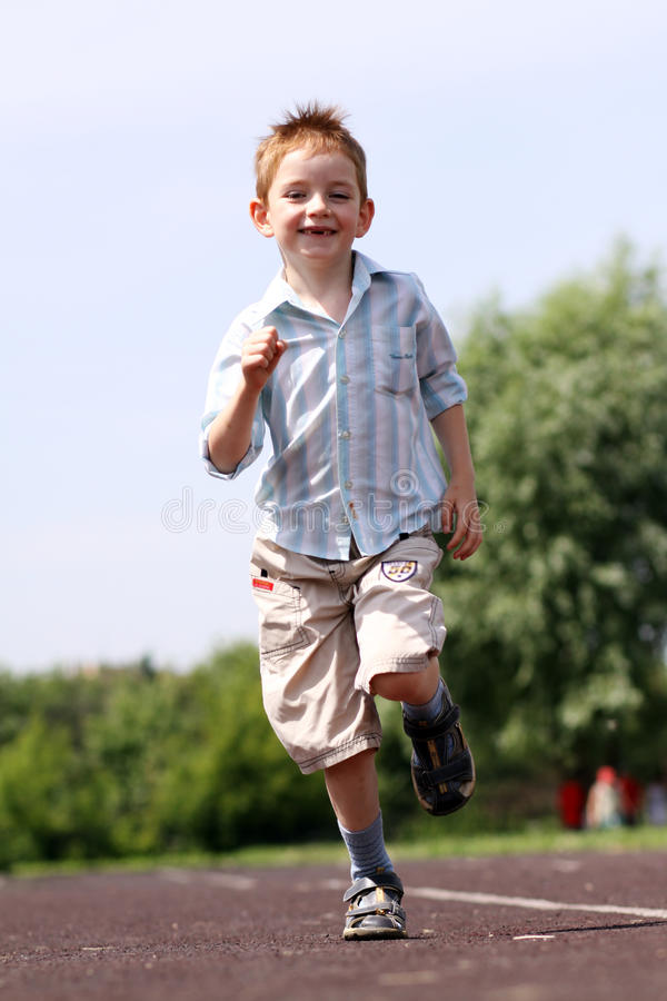 Esecuzioni del ragazzo in una sosta di estate immagini stock libere da diritti