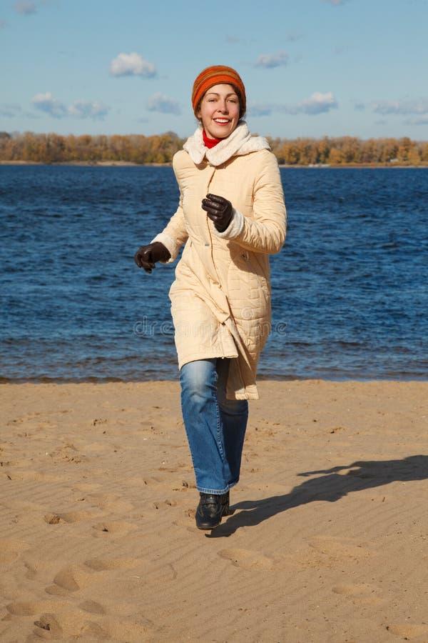 Esecuzioni della ragazza lungo il giorno di autunno della spiaggia. immagini stock