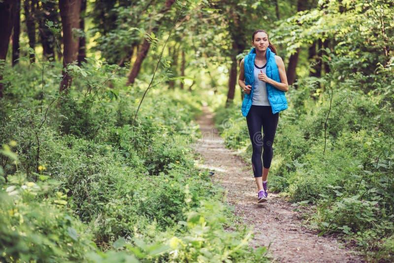 Eseguire allenamento macking della giovane bella donna sulla natura, parco, fondo della foresta Rivestimento senza maniche caldo  immagine stock libera da diritti