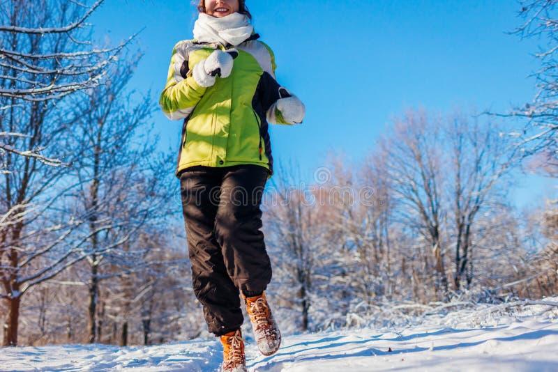 Eseguire la donna dell'atleta che sprinta nell'esterno di addestramento della foresta di inverno in tempo nevoso freddo immagine stock
