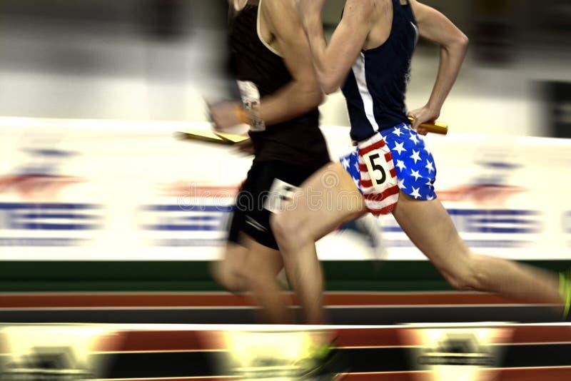 Eseguire una corsa di relè sugli shorts della bandiera del tratto immagine stock libera da diritti