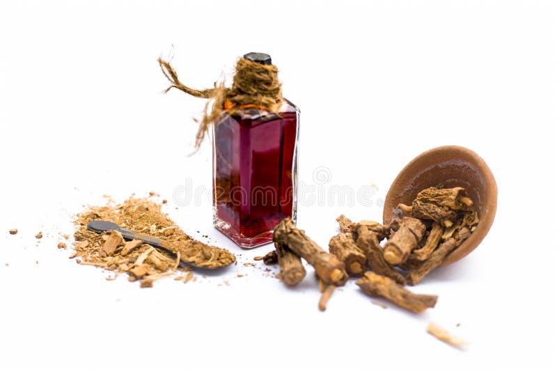 Esencia coloreada rojo oscuro del nannari o de la zarzaparrilla india en una botella transparente aislada en blanco foto de archivo