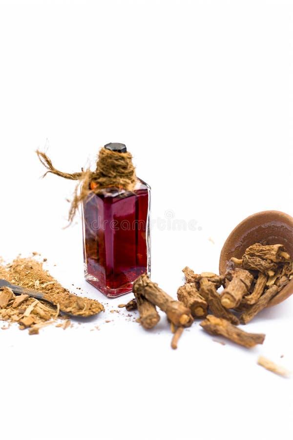 Esencia coloreada rojo oscuro del nannari o de la zarzaparrilla india en una botella transparente aislada en blanco fotografía de archivo libre de regalías