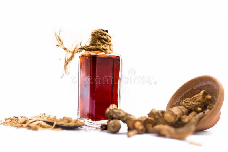 Esencia coloreada rojo oscuro del nannari o de la zarzaparrilla india en una botella transparente aislada en blanco fotografía de archivo
