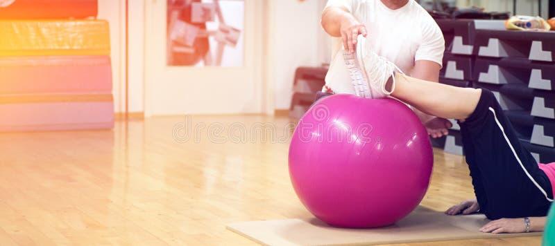 Esercitandosi con l'istruttore personale sulla grande palla di stabilità in parte posteriore di forma fisica dello studio immagini stock