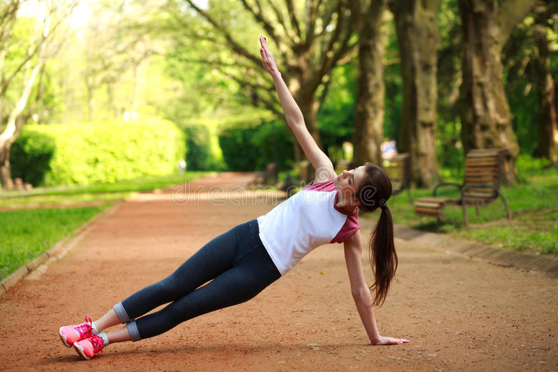Esercitazione allegra all'aperto in parco, addestramento della ragazza di forma fisica fotografia stock libera da diritti