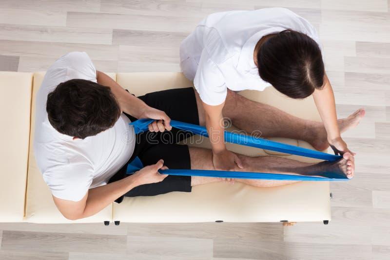 Esercitazione femminile di Assisting Patient While del terapista immagine stock