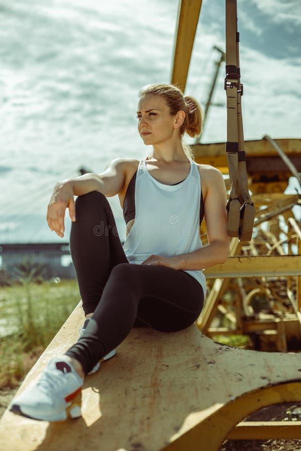Esercitazione femminile sportiva positiva con le strisce del trx immagine stock
