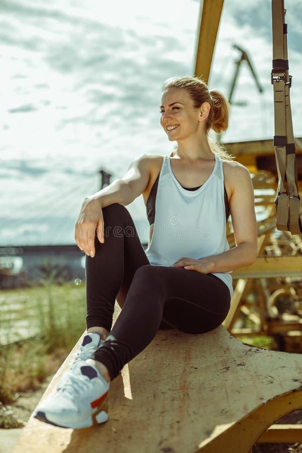 Esercitazione femminile sportiva positiva con le strisce del trx fotografie stock