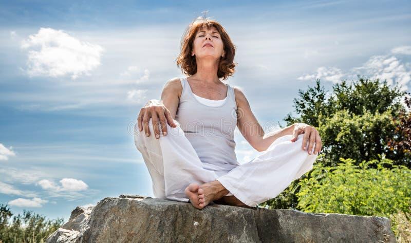 Esercitazione fuori per la donna radiante di yoga 50s che si siede sullo ston fotografie stock libere da diritti