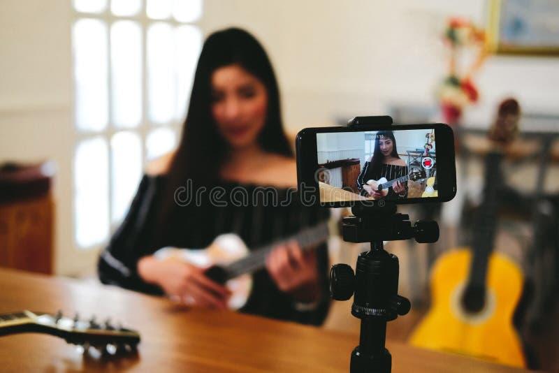 Esercitazione in tensione dello strumento di musica di radiodiffusione di blogger sui media sociali vlogger che registra il video fotografia stock libera da diritti