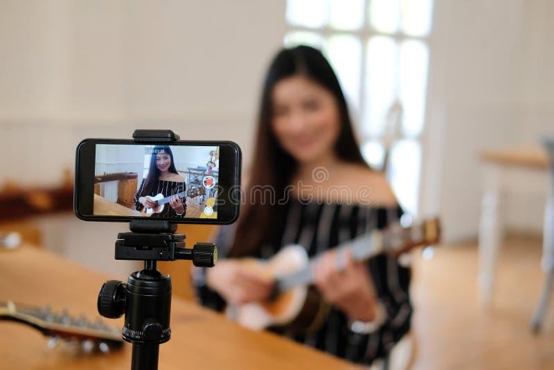Esercitazione in tensione dello strumento di musica di radiodiffusione di blogger sui media sociali vlogger che registra il video fotografia stock