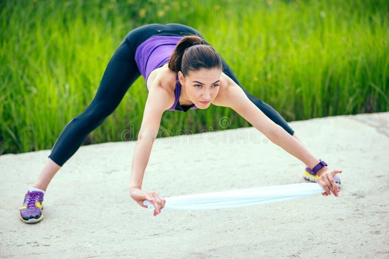 Esercizi di giovane allenamento sportivo attraente della donna nel parco con l'asciugamano bianco Priorità bassa della natura In  fotografie stock