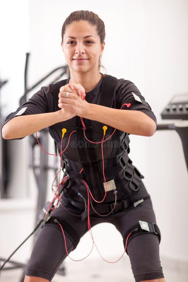 Esercizio adatto della donna sull'elettro donna muscolare fotografie stock