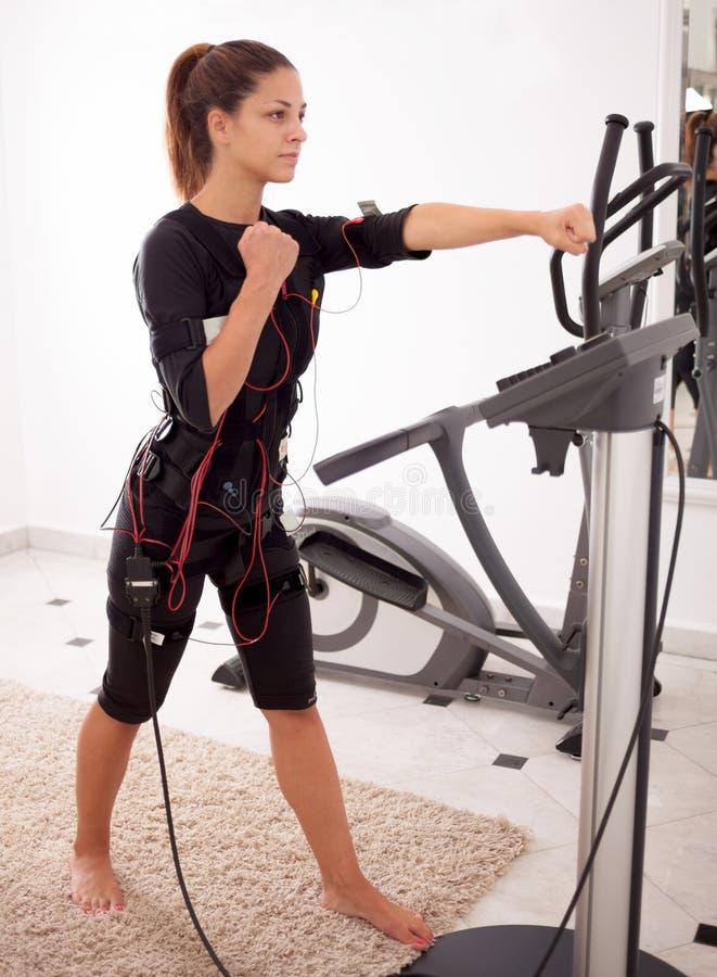 Esercizio adatto della donna sull'elettro donna muscolare fotografia stock