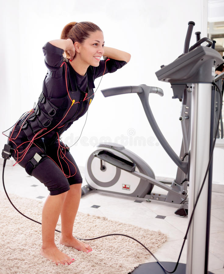 Esercizio adatto della donna sull'elettro donna muscolare fotografia stock libera da diritti