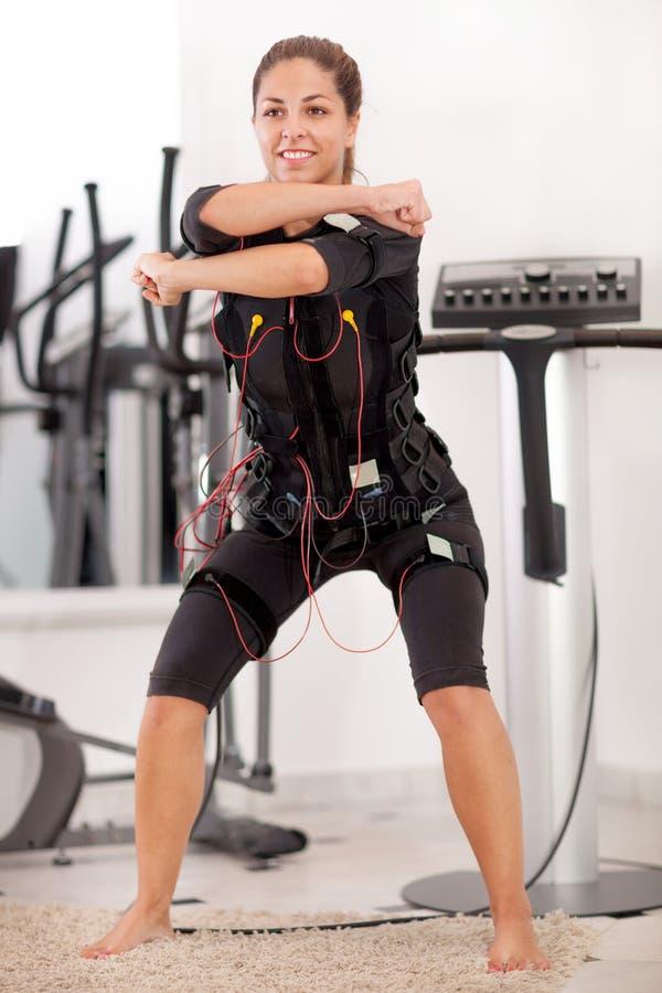 Esercizio adatto della donna sull'elettro macchina muscolare fotografia stock