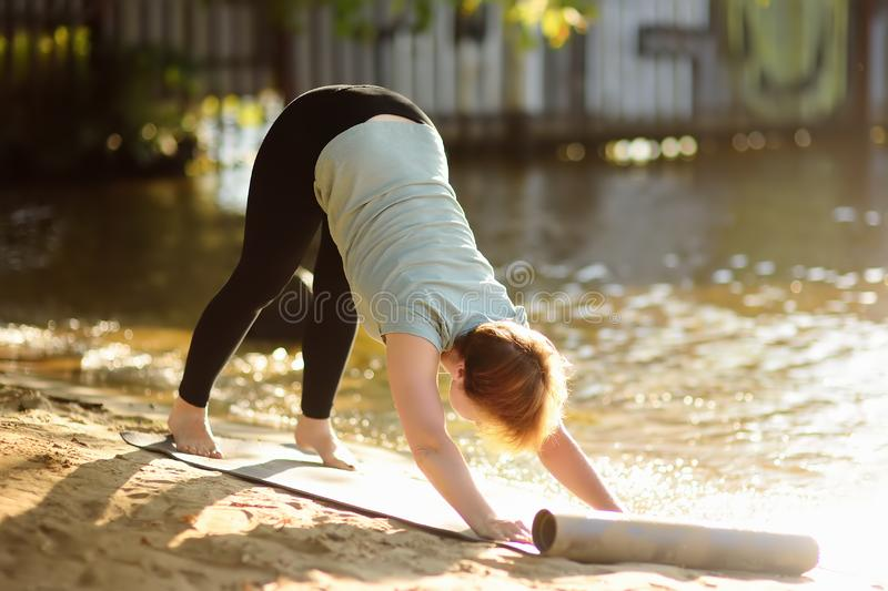 Esercizio all'aperto di pratica di yoga della donna matura sulla spiaggia vicino al fiume immagine stock