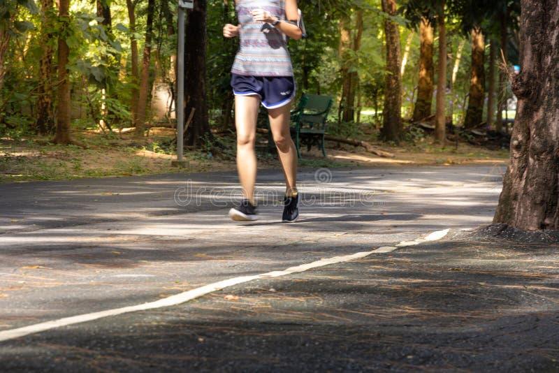 Esercizio corrente sulla strada in parco, concetto sano della donna dell'atleta immagine stock libera da diritti